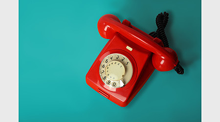 Red vintage phone on a blue background