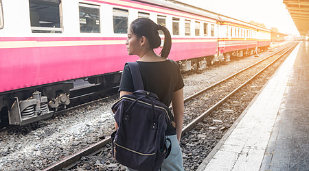 Lonely woman on train platform of railway station her feel homesick