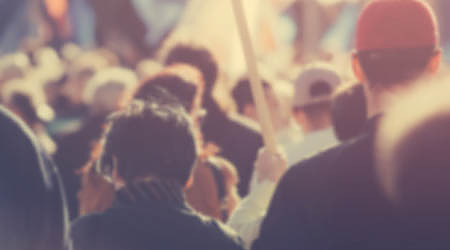Blur unrecognizable crowd at political meeting, cheering audience